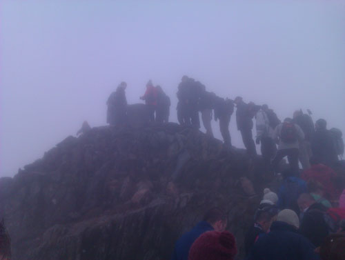 a crowd of walkers at a misty Snowdon summit