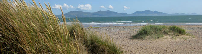 Sand dunes and Newborough Beach on Anglesey, looking across the Menai Strait to the mountains of Snowdonia